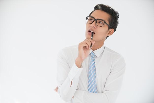 Pensive asian business man biting pen Photo gratuit