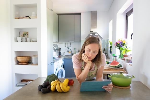 Pensive Woman Reading Recette Sur Tablette Tout En Cuisinant Dans Sa Cuisine, Regarder Des Cours De Cuisine En Ligne. Vue De Face. Cuisiner à La Maison Et Concept D'alimentation Saine Photo gratuit