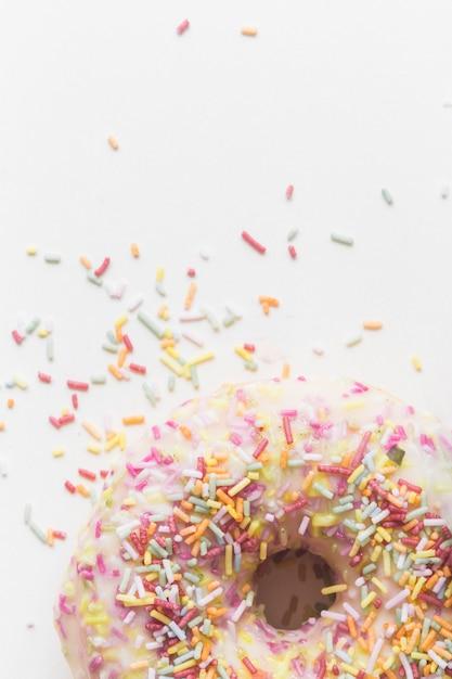 Pépites colorées sur le beignet sur fond blanc Photo gratuit