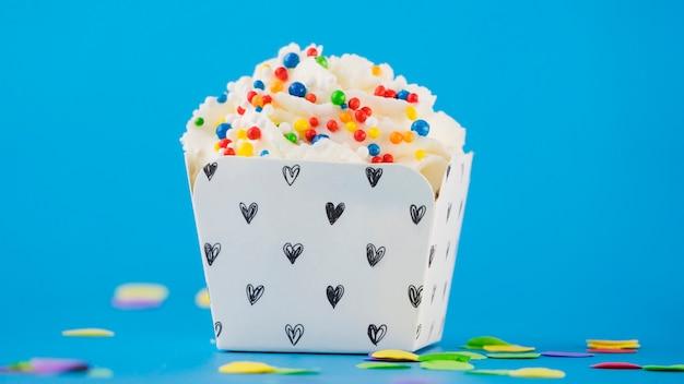 Pépites colorées sur la crème fouettée dans la boîte sur fond bleu Photo gratuit