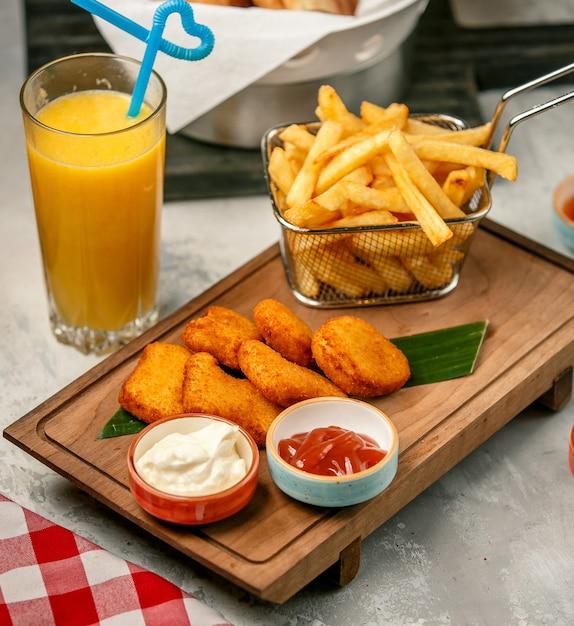 Pépites frites et frites sur planche de bois Photo gratuit