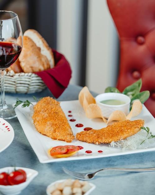 Pépites pépites de poisson servies avec une sauce spéciale et des frites Photo gratuit