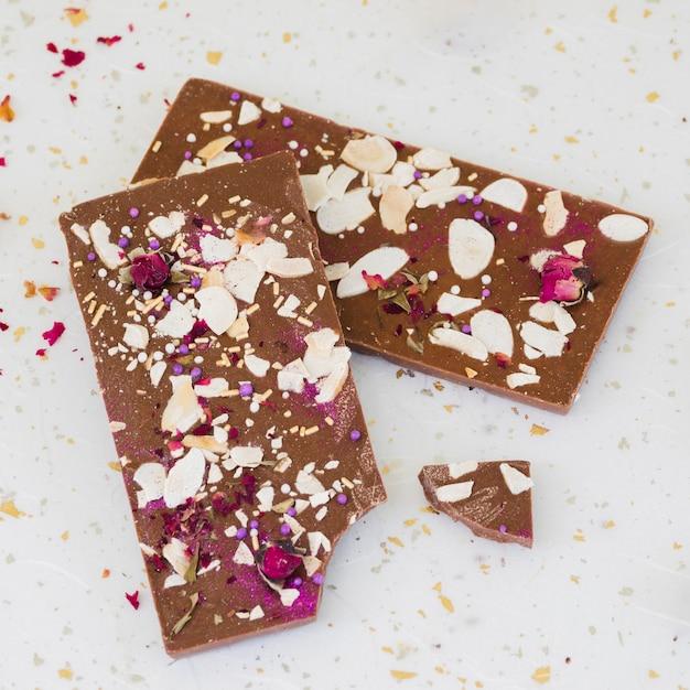 Pépites et pétales de rose sur tablette de chocolat Photo gratuit