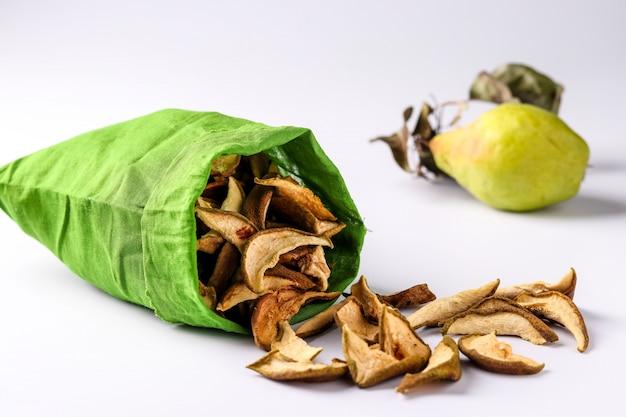 Pépites de poire dans un sac en coton et morceaux de ce fruit Photo Premium