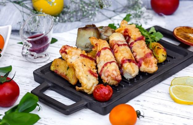Pépites De Poisson Croustillantes Servies Avec Potaot, Sauce à La Grenade Et Aubergine Frite Photo gratuit