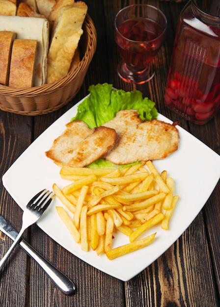 Pépites de poitrine de poulet rôties avec des frites dans une assiette blanche. Photo gratuit