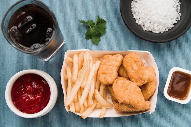 Pépites de poulet frit; frites; sauce tomate; coriandre; boisson gazeuse sur la table Photo gratuit