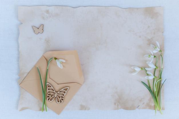 Perce-neige avec enveloppe et papier pour texte sur un fond en bois Photo Premium