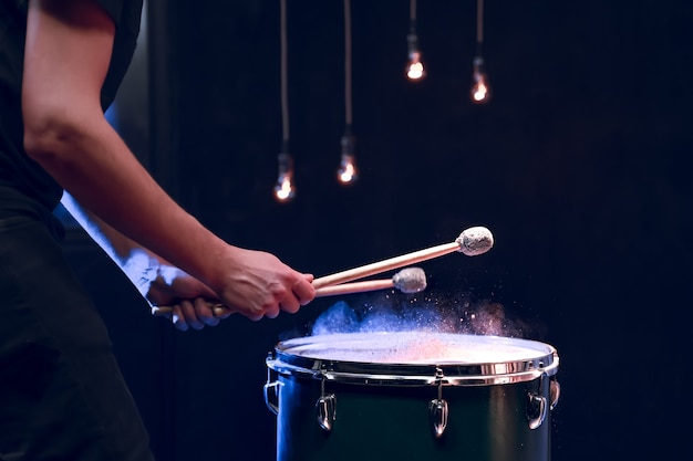 Le Percussionniste Joue Avec Des Bâtons Sur Le Tom Au Sol Dans Une Pièce Sombre Avec Un Bel éclairage. Concept De Concert Et De Performance. Photo gratuit