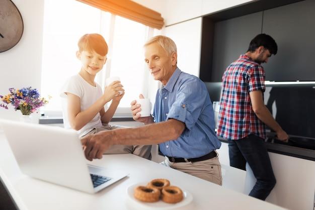 Un Père âgé Montre Quelque Chose Sur Un Ordinateur Portable à Son Fils. Photo Premium