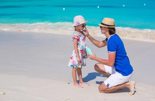 Père appliquer crème solaire sur le nez de sa petite fille Photo Premium