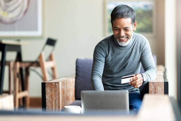 Père asiatique attrayant hipster barbu ou vieil homme hispanique à l'aide d'ordinateur portable et paiement par carte de crédit Photo Premium