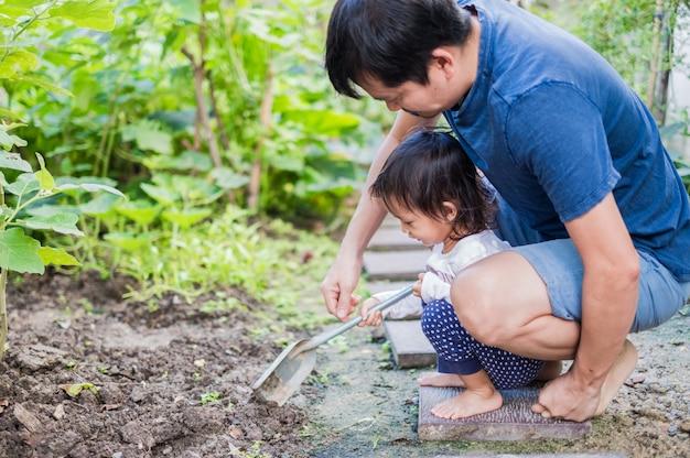 Père asiatique et sa fille dans le petit jardin de légumes à la maison. Photo Premium