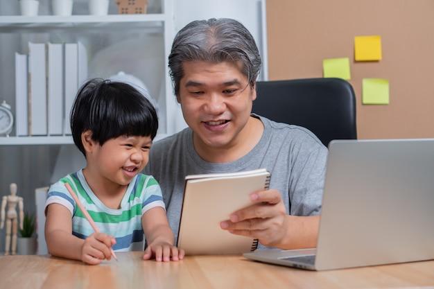 Père Asiatique Travaillant Au Bureau à Domicile Avec Un Ordinateur Portable Et Enseignant Les Devoirs Avec Une Fille. Photo Premium
