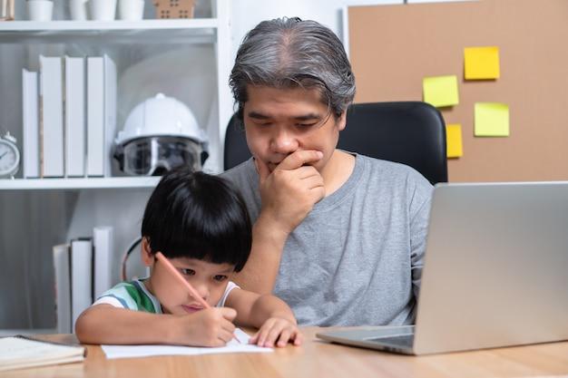 Un Père Asiatique Travaille à La Maison Avec Une Fille Et étudie L'apprentissage En Ligne à L'école Ensemble. Photo Premium