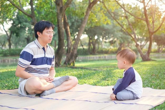 Père asiatique avec les yeux fermés et enfant de bambin âgé de 1 an pratique le yoga & méditer à l'extérieur sur la nature en été, concept de mode de vie sain Photo Premium