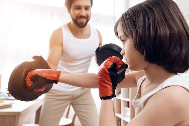Un père barbu apprend au jeune fils à boxer à la maison. Photo Premium