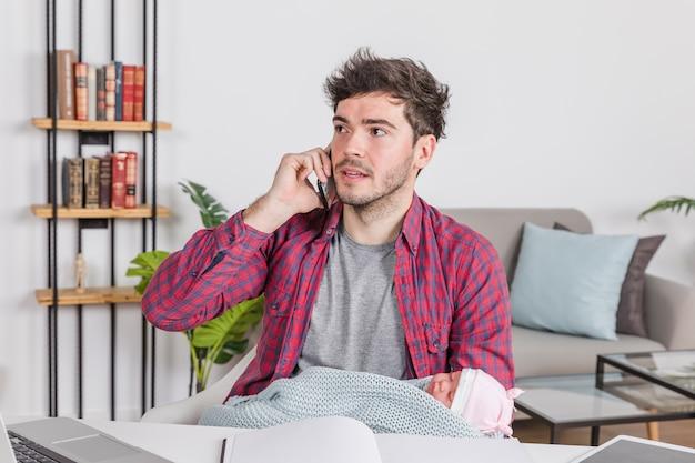 Père avec bébé parle au téléphone Photo gratuit