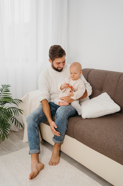 Père Sur Le Canapé Tenant Son Bébé à La Maison Photo gratuit
