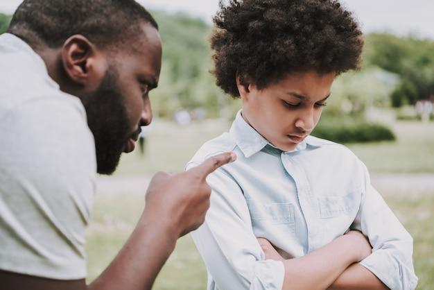 Un père en colère gronde un fils et un garçon qui se détournent de lui. Photo Premium