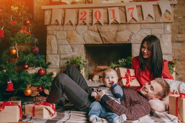 Père Couché Sur Les Genoux De Sa Femme Tout En Tenant Le Bébé Avec Un Bras Photo gratuit