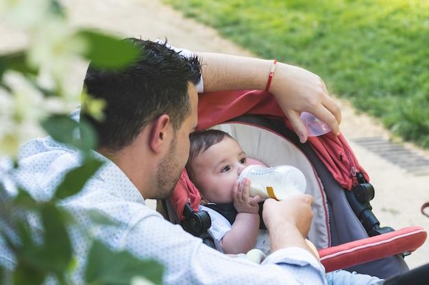 Père divorcé nourrir son bébé fils à l'extérieur. Photo Premium