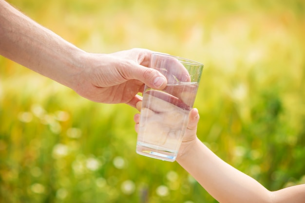 Le père donne à l'enfant un verre d'eau. mise au point sélective. Photo Premium