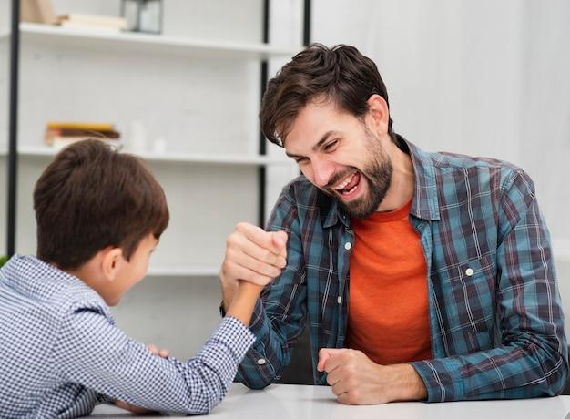 Père drôle faisant skandenberg avec son fils Photo gratuit