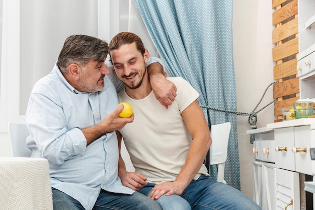 Père embrassant son fils et tenant une pomme savoureuse Photo gratuit