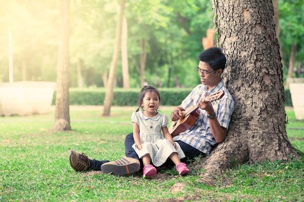 Père Et Enfant S'amuser à Jouer De La Guitare Ensemble Dans Le Parc Photo Premium