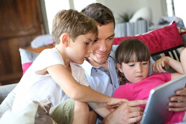 Père et enfants jouant avec une tablette à la maison Photo Premium