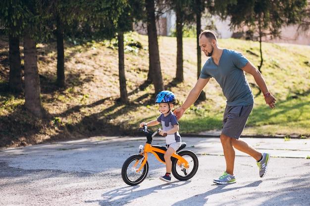 Père enseigne à son petit fils à faire du vélo Photo gratuit