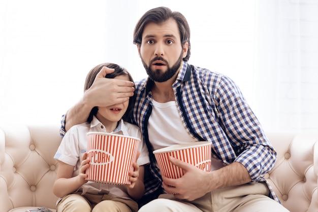 Père ferme les yeux de son fils en regardant un film d'horreur. Photo Premium