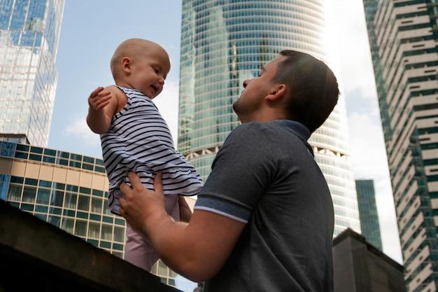 Père et fille d'un an contre le ciel et les gratte-ciels. voyager avec des enfants, le développement de l'intelligence émotionnelle. Photo Premium