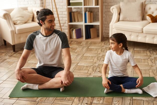 Père et fille en bonne santé sont assis dans une posture de lotus sur un tapis. Photo Premium