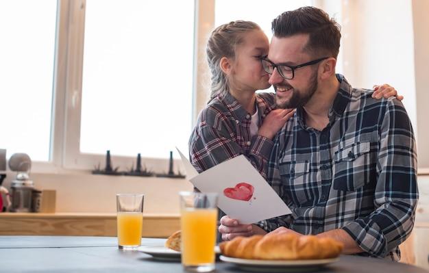 Père et fille ensemble sur la table du petit déjeuner Photo gratuit