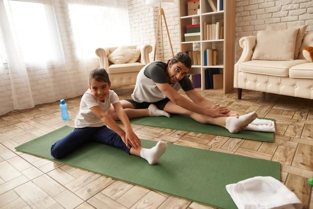 Père et fille étirent les jambes sur un tapis de gym. Photo Premium