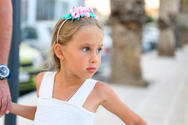 Père Et Fille. Une Jolie Petite Fille De Six Ans Tient La Main De Son Père En Se Promenant Dans La Rue De La Ville Photo Premium