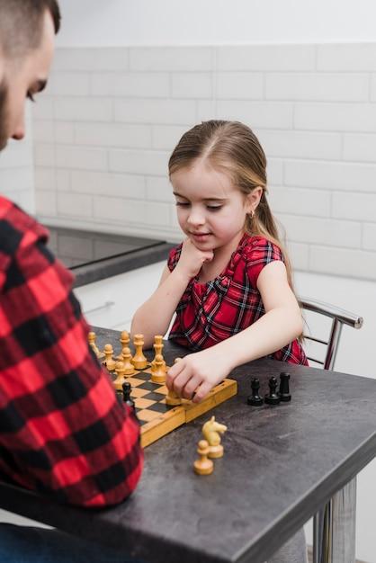 Père et fille jouant aux échecs le jour de la fête des pères Photo gratuit
