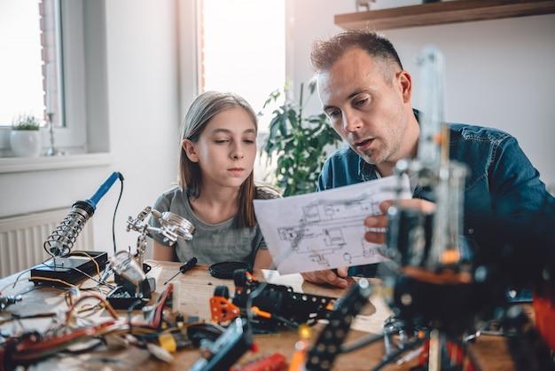 Père et fille regardant des schémas électroniques Photo Premium