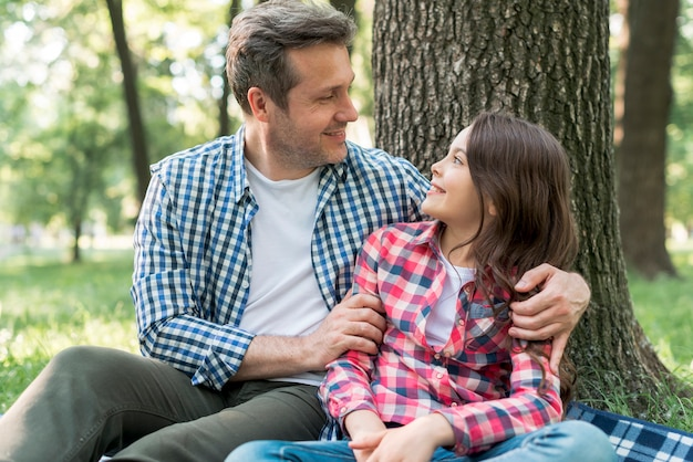 Père et fille se regardant assis près d'un arbre Photo gratuit
