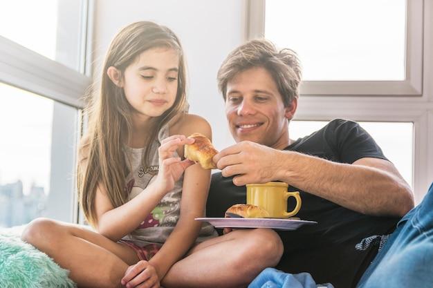 Père et fille avec une tasse de thé et des pains au petit déjeuner Photo gratuit