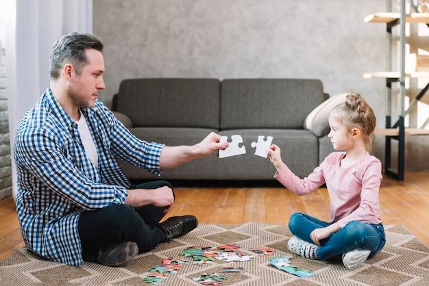 Père et fille tenant une pièce de puzzle Photo gratuit