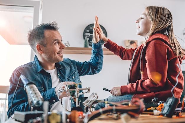 Père et fille travaillant sur des composants électroniques et acclamant Photo Premium
