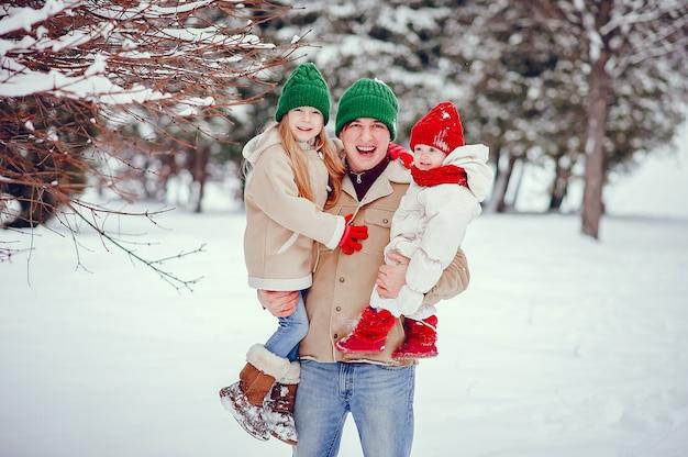 Père avec filles mignonnes dans un parc d'hiver Photo gratuit