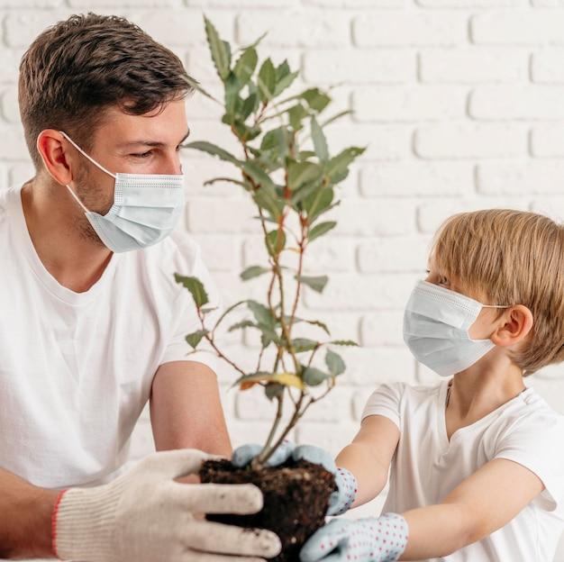 Père Et Fils Apprennent à Planter Ensemble à La Maison Tout En Portant Des Masques Médicaux Photo gratuit