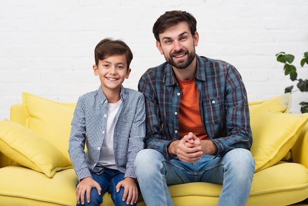 Père et fils assis sur un canapé et regardant un photographe Photo gratuit