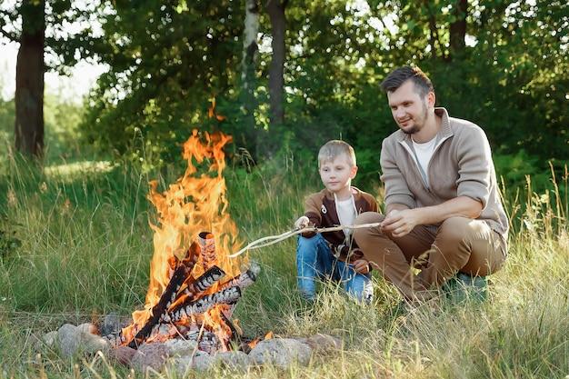 Père et fils au coin du feu sur la nature verte. Photo Premium