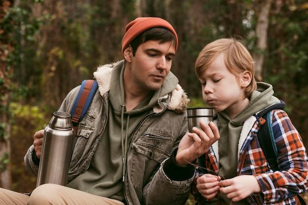 Père Et Fils Ayant Du Thé Chaud à L'extérieur Dans La Nature Photo gratuit