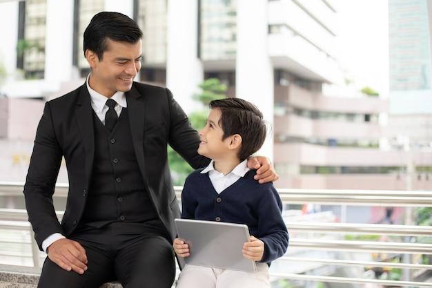 Père et fils célibataires jouant le jeu téléphone intelligent ensemble sur le quartier des affaires urbain Photo Premium